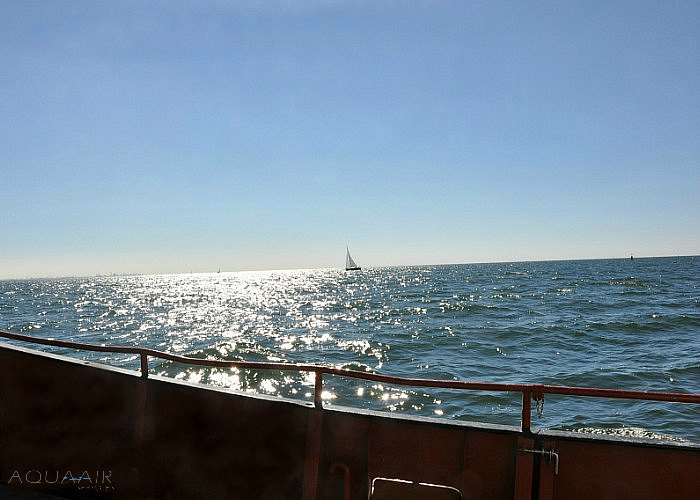 Scheveningen 2 op open zee voor een asverstrooiing met schittering van de zon op de zee